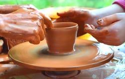 El amo enseña a una cerámica del niño La fabricación de productos de cerámica Trabajo en el taller de la cerámica Manos sucias en Foto de archivo
