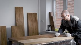 El amo está aplicando la laca en una superficie del los espacios en blanco de madera en un taller, sosteniendo la botella con los almacen de video