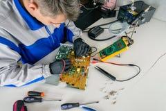 El amo está buscando el daño, mobiliario de oficinas de la reparación usando multímetro imágenes de archivo libres de regalías
