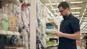 El amo está eligiendo un cable de extensión en un supermercado, sosteniendo uno en manos almacen de video