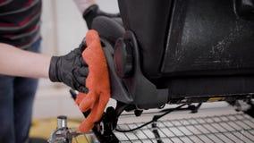 El amo está limpiando asientos autos y está manchando las colocaciones por el aceite en el auto-servicio, limpieza de automóviles almacen de video