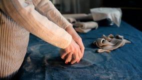 El amo forma la cerámica en una lona azul Proceso creativo Da forma a su producto metrajes