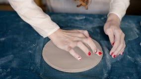 El amo forma la cerámica en una lona azul Proceso creativo Da forma a su producto Aumenta el borde de la placa del almacen de video