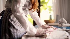 El amo forma la cerámica en una lona azul Proceso creativo Da forma a su producto Separe la arcilla con un rodillo metrajes