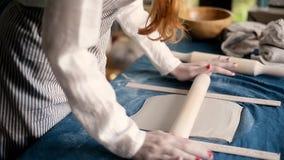 El amo forma la cerámica en una lona azul Proceso creativo Da forma a su producto Separe la arcilla con un rodillo almacen de video