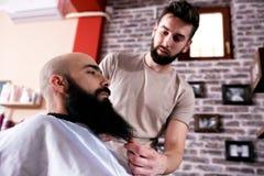 El amo hace la corrección de las barbas en salón de la barbería imagenes de archivo