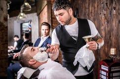 El amo hace la corrección de las barbas en salón de la barbería Ciérrese encima de la foto fotos de archivo