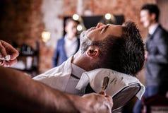 El amo hace la corrección de las barbas en salón de la barbería Ciérrese encima de la foto imagenes de archivo