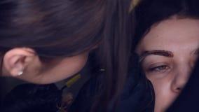 El amo hace las cejas Laminaci?n de la ceja La muchacha hace las cejas en el sal?n Forma hermosa de la ceja Fuga profesional de l almacen de metraje de vídeo