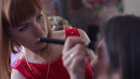 El amo hace maquillaje a la muchacha en el salón de belleza metrajes