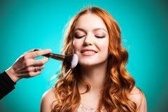 El amo inflige el polvo del cepillo en la cara de la muchacha fotografía de archivo