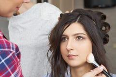 El amo inflige el polvo del cepillo en la cara de la muchacha, termina el maquillaje del día en un salón de belleza foto de archivo