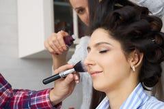 El amo inflige el polvo del cepillo en la cara de la muchacha, termina el maquillaje del día en un salón de belleza fotografía de archivo libre de regalías