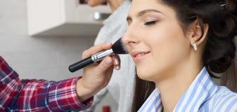 El amo inflige el polvo del cepillo en la cara de la muchacha, termina el maquillaje del día en un salón de belleza imagen de archivo