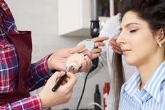 El amo inflige el polvo del cepillo en la cara de la muchacha, termina el maquillaje del día en un salón de belleza imágenes de archivo libres de regalías