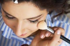 El amo inflige el polvo del cepillo en la cara de la muchacha, termina el maquillaje del día en un salón de belleza Estilista en  foto de archivo libre de regalías