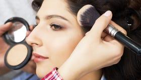 El amo inflige el polvo del cepillo en la cara de la muchacha, termina el maquillaje del día en un salón de belleza Estilista en  fotografía de archivo