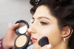 El amo inflige el polvo del cepillo en la cara de la muchacha, termina el maquillaje del día en un salón de belleza Estilista en  fotos de archivo libres de regalías