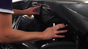 El amo instala la película del tinte para el vidrio del coche con el hairdryer y la espátula con el resplandor de la luz Teñido d almacen de video