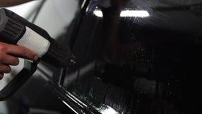 El amo instala la película del tinte para el vidrio del coche con el hairdryer y la espátula con el resplandor de la luz Teñido d almacen de metraje de vídeo