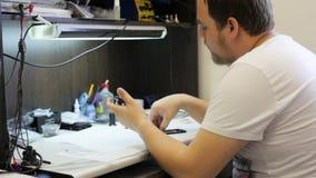 El amo masculino inserta la batería y terminado montando un teléfono celular almacen de metraje de vídeo