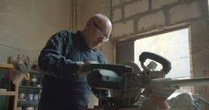 El amo masculino mayor trabaja en la fábrica de madera que presiona el tronzador que corta la madera almacen de video