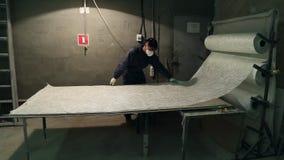 El amo mide la fibra de vidrio para cortar metrajes