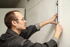 El amo mide la pared. Imagen de archivo libre de regalías
