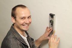 El amo mide la pared. Fotografía de archivo libre de regalías