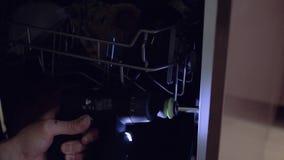 El amo, que fabrica los muebles fija el lavaplatos, usando un destornillador almacen de metraje de vídeo