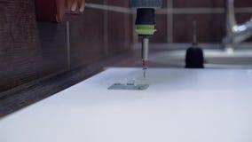 El amo, que fabrica los muebles fija el lavaplatos, usando un destornillador Primer almacen de metraje de vídeo