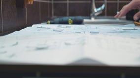 El amo, que produce e instala los muebles, exhibe un dibujo en la tabla almacen de metraje de vídeo