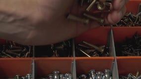 El amo que produce e instala los muebles vierte muchos pernos en la célula en la maleta Primer Cámara lenta almacen de video