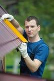 el amo repara el tejado de una casa Foto de archivo libre de regalías