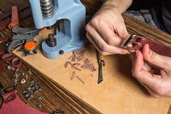 El amo sostiene una placa y un pedazo de cuero En la tabla de madera marrón dispersó con las herramientas y los accesorios Fotos de archivo