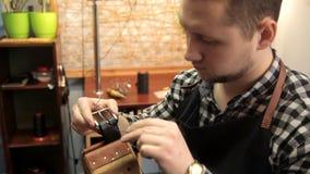 El amo sujeta la hebilla en la correa de cuero, cose una aguja Procedimiento para la fabricación de correas de cuero metrajes