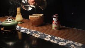 El amo vierte el agua especialmente preparada para cocinar el té japonés Matthia