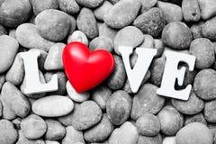 El amor de la palabra con el corazón rojo en piedras del guijarro Foto de archivo libre de regalías