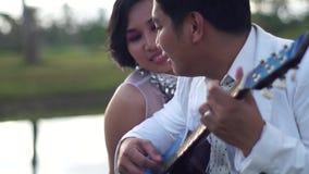 El amor de las serenatas del hombre joven con la mujer de la guitarra mira al novio almacen de metraje de vídeo