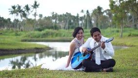 El amor de las serenatas del hombre joven con la mujer de la guitarra mira al novio almacen de video