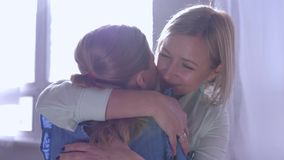 El amor de madre, niña acomete en las manos de la mamá y da el abrazo grande y se besa en casa contra ventana en rayos del sol almacen de metraje de vídeo