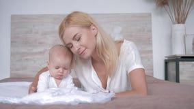El amor de madre, padre joven besa el bebé recién nacido y la mirada in camera que mienten en cama en casa metrajes