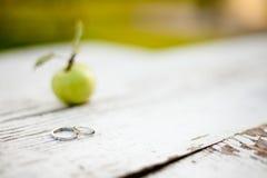 El amor está en la manzana, anillos de bodas fotos de archivo