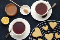 El amor formó las galletas para el día de tarjetas del día de San Valentín y dos tazas de té en la tabla Foto de archivo