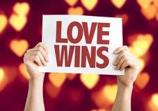 El amor gana la tarjeta con el fondo del bokeh Imagen de archivo