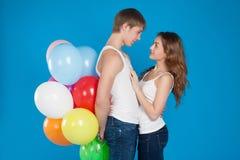 El amor joven sonriente junta sostener los globos en el estudio Fotografía de archivo libre de regalías