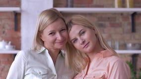 El amor para la madre, retrato de la hija hermosa adulta de la familia feliz besa la mamá afortunada en mejilla y la mirada en ci almacen de video