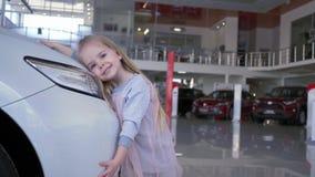 El amor para los coches, muchacha sonriente feliz del niño abraza la linterna del automóvil en la sala de exposición auto almacen de metraje de vídeo