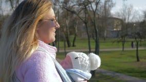 El amor parental, madre afortunada en las lentes con el pequeño hijo en las manos camina en parque metrajes