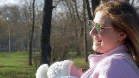 El amor parental, madre alegre cuida para el bebé en brazos al aire libre en primavera los fines de semana almacen de metraje de vídeo